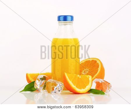 bottled orange juice in the bottle with blue lid and with ice cubes and fresh oranges