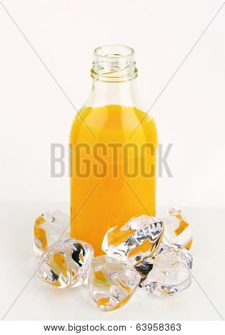 refreshing orange juice in the glass bottle with ice cubes