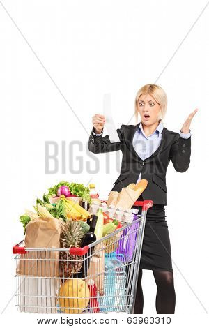Formal woman looking at the shopping bill in disbelief isolated on white background