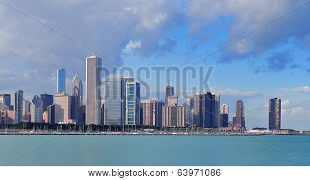Chicago skyline panorama with skyscrapers over Lake Michigan with cloudy blue sky.