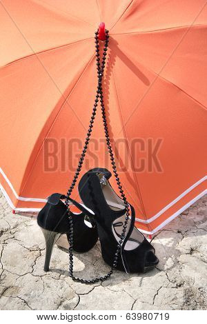 Stiletto Heels, Necklace And Umbrella On A Cracked Earth