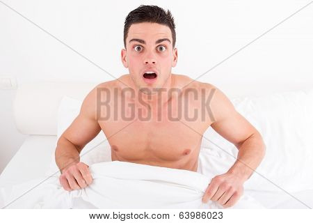 Shocked Half Naked Young Man In Bed  Looking Down At His Underwear