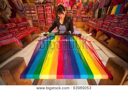Chinese Naxi Woman Weaving Shown To Tourists In Lijiang Dayan Old Town.