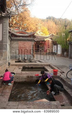 Chinese Naxi Woman Washing On Ancient Pool Is White Horse Dragon Pool.