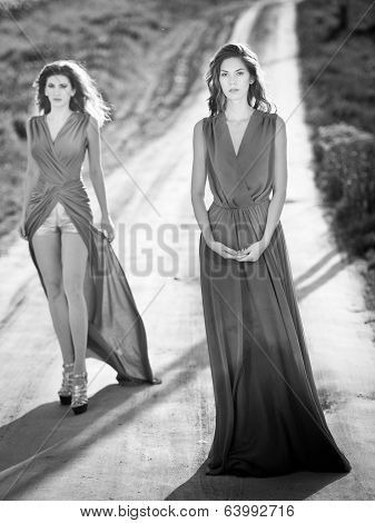 Two young fashionable women waking on country side road, black and white photo. Attractive women