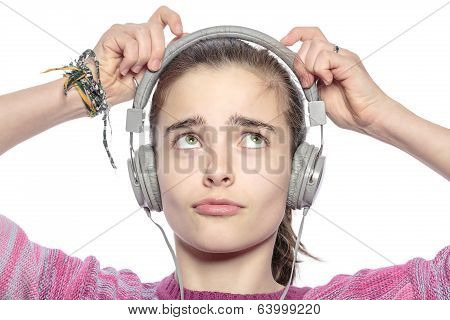 Beautiful Teenager Girl Fumble On Her Headphones, Isolated On White