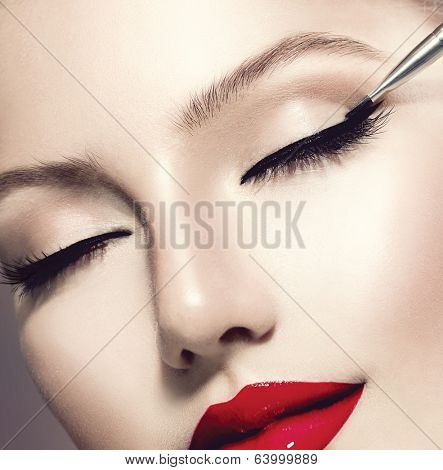 Makeup. Perfect Make-up Applying closeup. Eyeliner. Cosmetic Eyeshadows. Eyeline brush for Make up. Beauty Girl with Perfect Skin. Eyelashes. Red Lipstick. Makeover