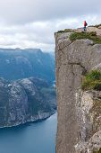 stock photo of cliffs  - Woman hiker standing on cliff of Pulpit Rock  - JPG