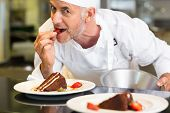 image of pastry chef  - Closeup portrait of a smiling male pastry chef eating strawberry by dessert in the kitchen - JPG
