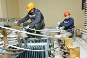 image of lineman  - Electrician lineman repairman worker at huge power industrial transformer installation work - JPG