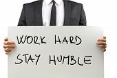 pic of humble  - Close up torso view isolated on white of a businessman in a suit holding a handwritten sign with a motivational message saying  - JPG