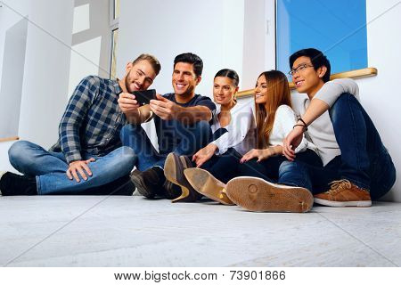 Portrait of a happy friends sitting on the floor and looking at smartphone