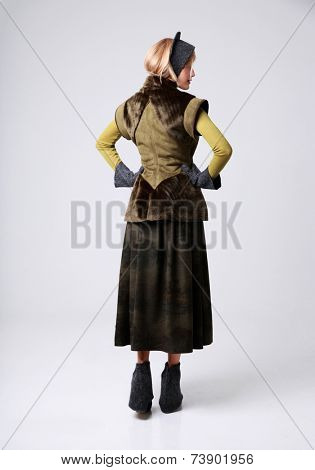 Back view portrait of a trendy woman over gray background