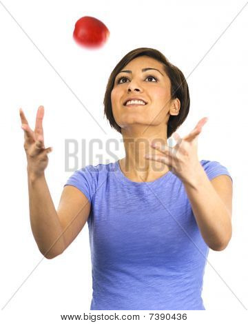 Young Woman Tosses Apple Into Air.
