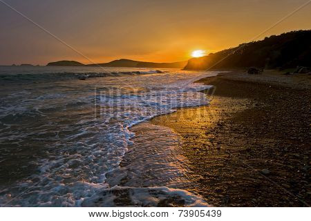 waves on the beach against sunset of russian isle Putyatin