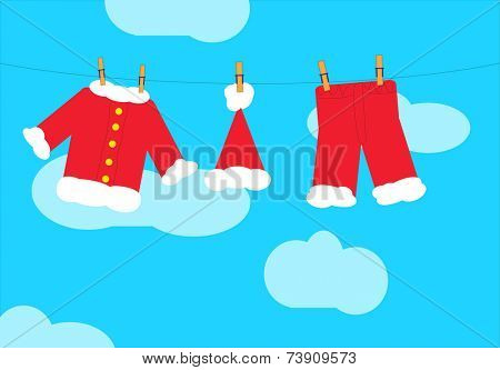 Santa Claus clothes on a clothesline with a blue sky with clouds in background.  EPS vector format.