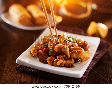 eating colorful chinese general tso's chicken with chopsticks