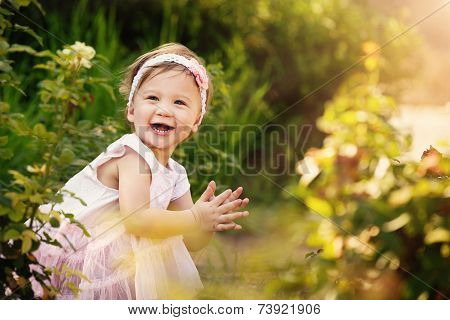 Beautiful Toddler In Garden Smiling And Clapping