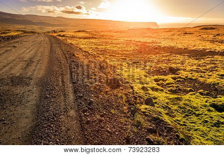 Gravel road through a barren landscape of Westfjords in Iceland