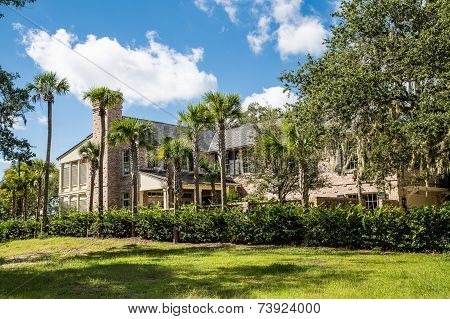 Brown Brick Mansion With Palm Trees Under Blue Sky