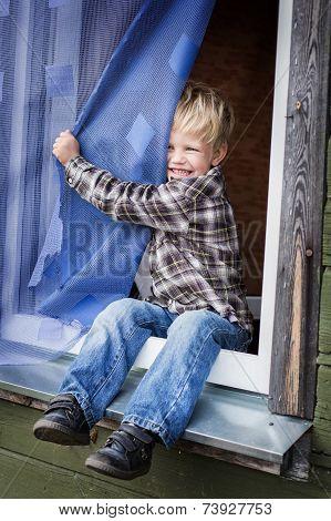 Beautiful blond kid sitting on window sill
