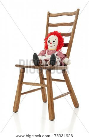 A rag doll alone on a ladder-back chair.  Isolated on white.