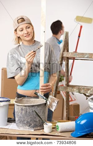 Happy casual, caucasian couple busy renovating painting new home. Baseball cap, bucket, ladder.