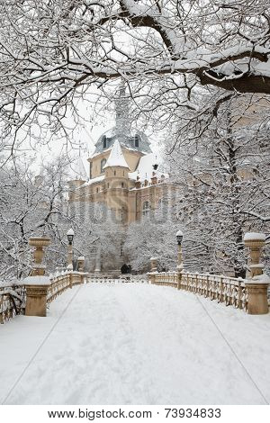 Snow covered mansion at empty winter park outdoor. Vintage yellow building, trees and bridge.