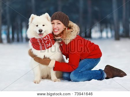 Joyful Beautiful Stylishly Dressed Young Woman In Red Jacket Hugging White Samoyed Dog