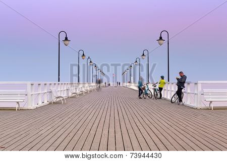 GDYNIA, POLAND - 3 OCTOBER 2014: Baltic pier in Gdynia Orlowo at sunset, Poland. This wooden pier at Baltic sea, long for 180 meters is tourist attraction in Gdynia.