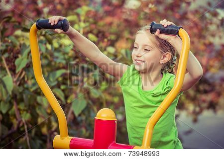 Young smiling girl does exercises at simulator in park