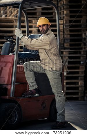 Warehouse worker climbing into fork lift