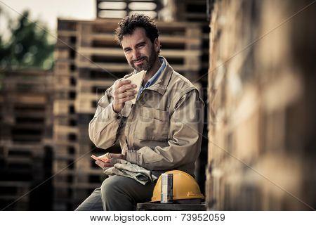 Warehouse worker sitting on pallets for a lunch break