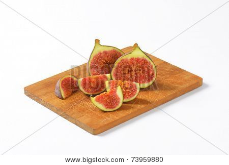 freshly halved figs with pink pulp, served on the wooden cutting board