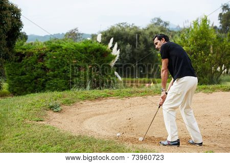 Man in sports clothing playing golf while standing golf sand