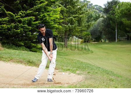 Golfer on sand trap hitting golf ball to the hole