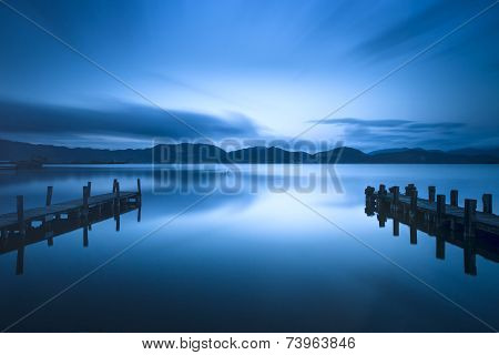 Two Wooden Pier Or Jetty And On A Blue Lake Sunset And Sky Reflection On Water. Versilia Tuscany, It