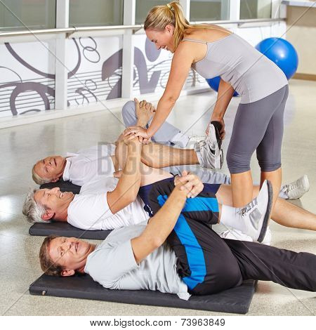Three senior people doing gymnastics in fitness center with instructor