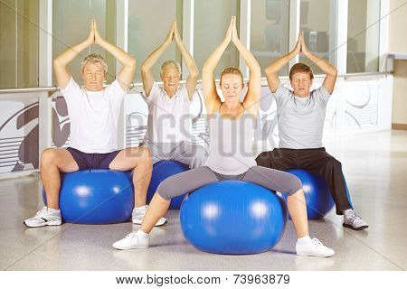 Senior group exercising in yoga class in gym