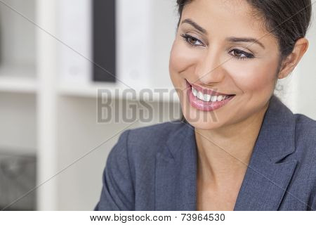 Portrait of a successful beautiful young Latina Hispanic woman or businesswoman in her office smiling with perfect teeth