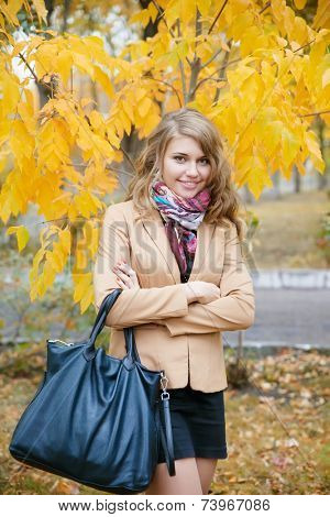 Young beautiful woman at the autumn park