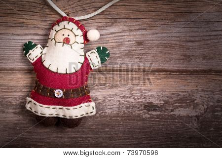 Hand made felt Santa Claus Christmas decoration. Vintage style, over old wood background, with space for your text.
