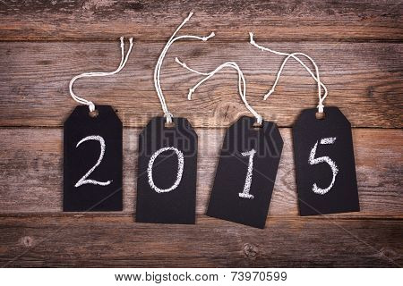 Chalkboard gift tags with strings, over old wood background, 2015 written in white chalk. New Year 2015 concept.