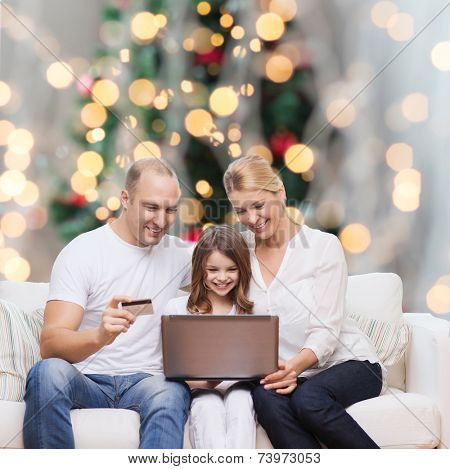 family, holidays, shopping, technology and people concept - happy family with laptop computer and credit card over christmas lights tree background