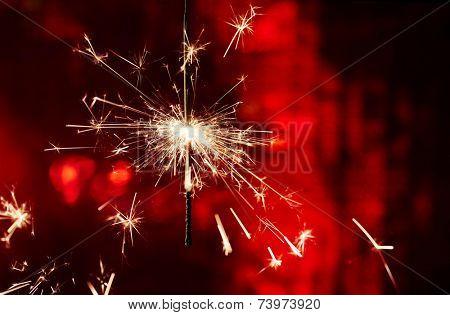 Sparkler on red background