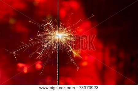Sparkler on red background