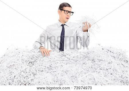 Worried man covered in shredded paper isolated on white background