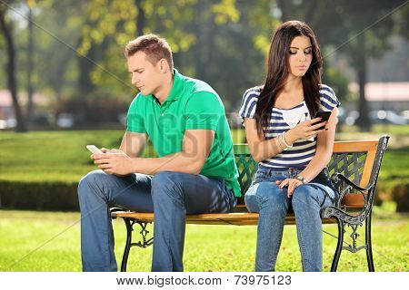 Conflicted couple not talking to each other seated on a wooden bench in park