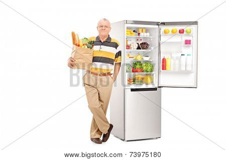 Man holding bag with groceries by an open fridge isolated on white background