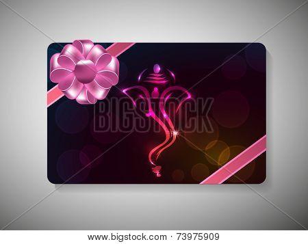 Diwali festival gift card with shiny face of Lord Ganesha and ribbon decoration on stylish background.